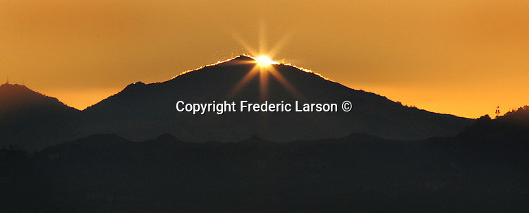 The sun peaks over Mount Diablo in the East Bay of California.