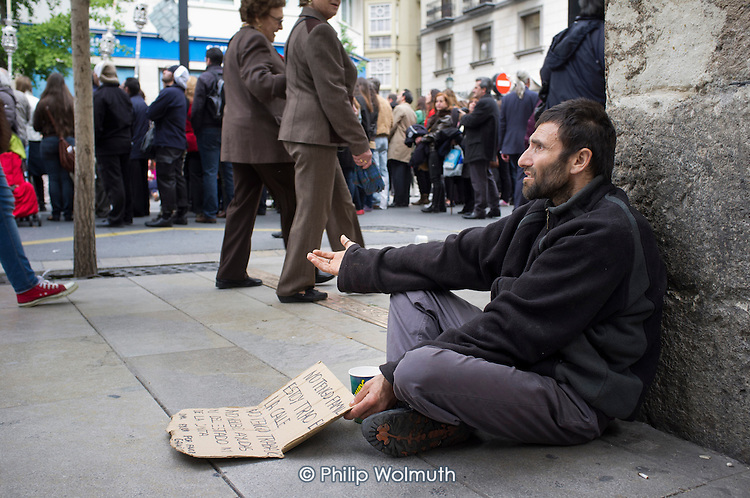 A homeless man begs on a street corner during a religious parade in Granada, Spain.