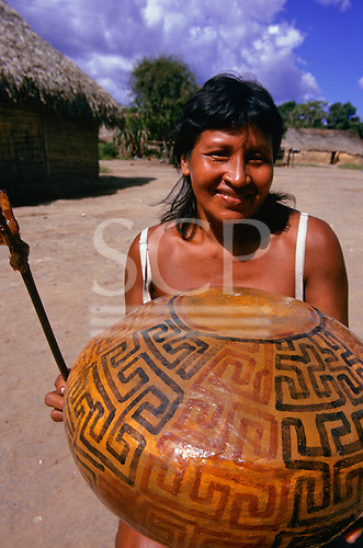 Koatinemo village, Brazil. Assurini woman holding a pot decorated with typical geometric design and stick with resin glaze.