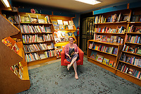 NWA Media/ J.T. Wampler - Lisa Sharp, owner of Nightbird Books in downtown Fayetteville, sits in the  children's book section Wednesday August 27, 2014.