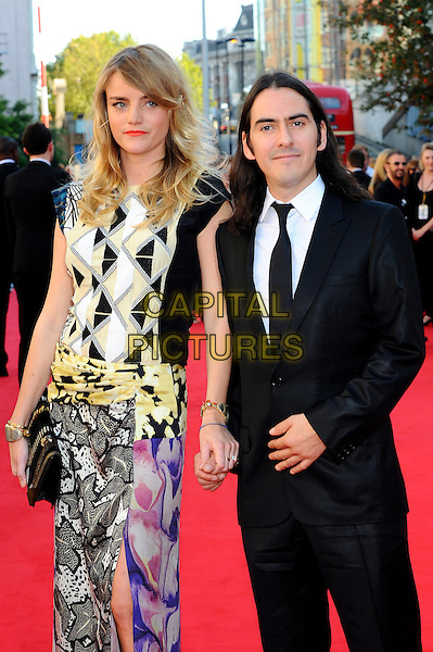 guest & Dhani Harrison.Arrivals to the UK Premiere of 'George Harrison: Living In The Material World' at BFI Southbank, London, England..October 2nd, 2011.half length suit white purple pink print dress holding hands black white tie.CAP/CJ.©Chris Joseph/Capital Pictures.