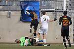 15 December 2013: Notre Dame's Connor Klekota (3) steps on the ankle of Maryland's Zack Steffen (in green) as Maryland's Chris Odoi-Atsem (28) jumps over. The University of Maryland Terripans played the University of Notre Dame Fighting Irish at PPL Park in Chester, Pennsylvania in a 2013 NCAA Division I Men's College Cup championship match. Notre Dame won the game 2-1.
