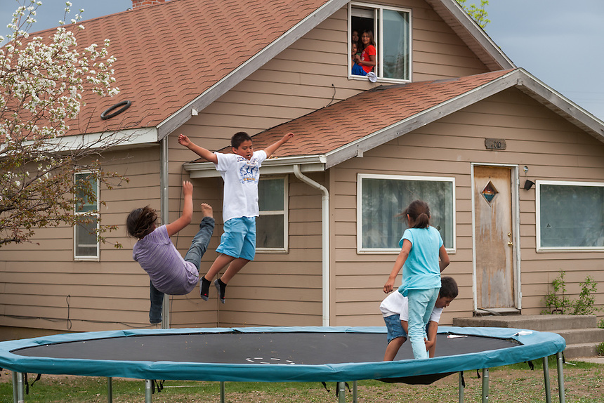 Kids play on a trampoline on the Crow Reservation at Crow Agency, Montana, Thursday, May 16, 2013. Pending new ports for shipment to Asia through either the U.S. or Canada, Cloud Peak Energey hopes to open new high-grade coal mines on and near the Crow Reservation in southern Montana. The tribe is equally hopeful the new mines would bring long-awaited economic stability to the tribe. (Kevin Moloney for the New York Times)