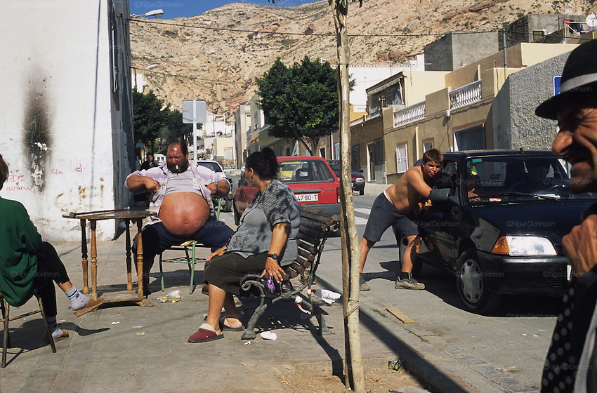 Gitanos sitting in the square of Pescadera barrio. Whilst some find work as fishermen on  huge trawlers, many are caught up in poverty, and others crack addicts. Almeria, Spain 2001