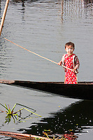 Myanmar, Burma.  Little Burmese Child of Intha Ethnic Group Standing in a Canoe, Inle Lake, Shan State.  She has a light coating of thanaka paste on her face, a cosmetic sunscreen.