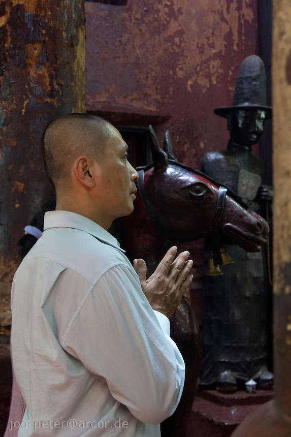 man praying in Chua Ngoc Hoang temple in Ho Chi Minh City / Saigon,  Vietnam. Taoist temple Phouc Hai Tu (turtle sanctuary) is called Cua Ngoc Hoang (Jade emperor) by the peope. Vietnamese belief is a blend of Buddhism, Taoism and animism