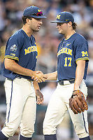 Michigan Wolverines pitcher Jeff Criswell (17) is greeted by teammate Jack Bredeson (34) against the Vanderbilt Commodores during Game 3 of the NCAA College World Series Finals on June 26, 2019 at TD Ameritrade Park in Omaha, Nebraska. Vanderbilt defeated Michigan 8-2 to win the National Championship. (Andrew Woolley/Four Seam Images)