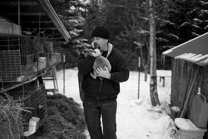 Jeff Stankiewicz holds a rabbit outside his cabin in northern Idaho, where he lives with wife Leslie Brown-Jeff Stankiewicz. They raise their own chickens and rabbits in an effort to live sustainably and prepare for a doomsday scenario when they would no longer be able to obtain groceries.