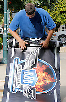 NWA Democrat-Gazette/DAVID GOTTSCHALK  Josh Underhill, with Signarama of Johnson, prepares a banner promoting Bikes, Blues and BBQ Monday, September 14, 2015 to hang over Dickson Street in Fayetteville. The 16th annual motorcycle rally runs September 23-26.