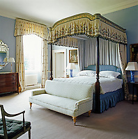 The master bedroom is furnished with a mahogany four-poster bed and traditional bed hangings
