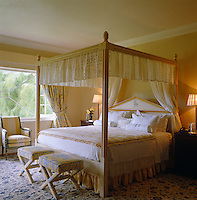 This romantic and feminine bedroom features a four-poster bed with a broderie anglaise trim