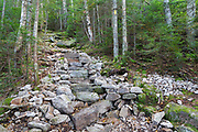 Rock steps along the Mount Tecumseh Trail in the New Hampshire White Mountains. Trail maintenance handbooks suggest the best trails show little evidence of work and that work should blend in with its surroundings.