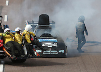Feb 21, 2015; Chandler, AZ, USA; NHRA funny car driver Shane Westerfield walks away after suffering an engine fire during qualifying for the Carquest Nationals at Wild Horse Pass Motorsports Park. Mandatory Credit: Mark J. Rebilas-