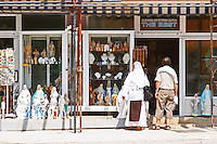 A shop with souvenirs for pilgrims, called 'The Best'. A nun in white looking at the things for sale. Madonna statue, rosary beads. Medugorje pilgrimage village, near Mostar. Medjugorje. Federation Bosne i Hercegovine. Bosnia Herzegovina, Europe.
