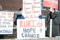 A man displays signs comparing Republican presidential candidate Marco Rubio to Barack Obama outside Manchester's Ward 1 polling location at Webster Elementary School in Manchester, New Hampshire, on the day of primary voting, Feb. 9, 2016.