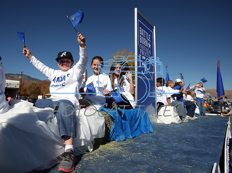 Kids on the NV-150 Sesquicentennial float wave at the crowd during the 75th annual Nevada Day parade in Carson City, Nev., on Saturday, Oct. 26, 2013.<br /> Photo by Cathleen Allison