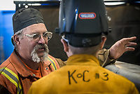 Applied Technology instructor James Selkirk discusses boat building techniques with new welding student Chris Gilbert inside the Industrial Arts Building at UAA's Kodiak College.