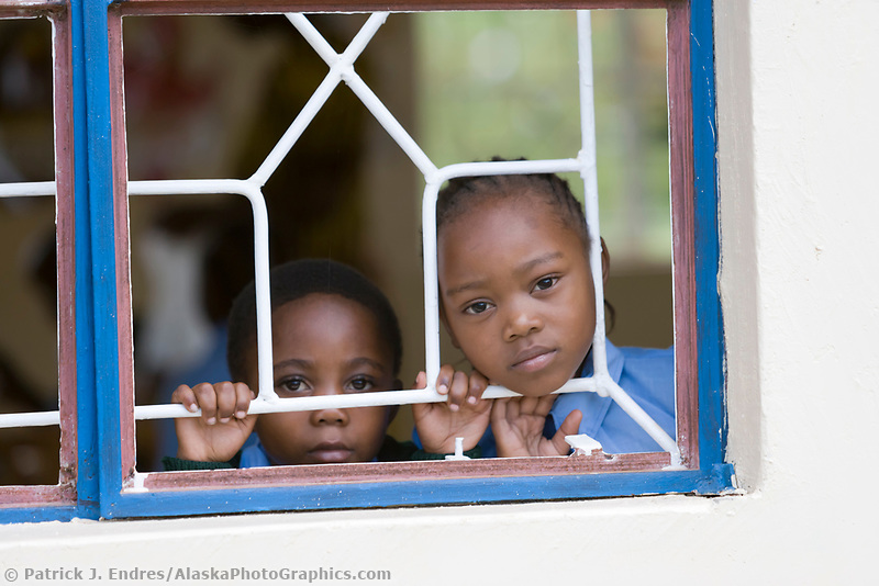 Young children peer through a school classroom window in the small village of Usa River, Tanzania, East Africa
