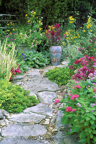 Rock pathway curves  through blooming garden of mult-colored blooms and herbs with painted Mexican ceramic pot