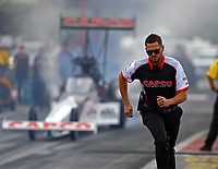Apr 21, 2018; Baytown, TX, USA; NHRA top fuel driver Steve Torrence does a burnout as crew member Gary Pritchett runs alongside during qualifying for the Springnationals at Royal Purple Raceway. Mandatory Credit: Mark J. Rebilas-USA TODAY Sports