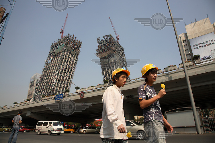 Two migrant workers eat ice lollies on a break in front of the new China Central Television (CCTV) tower designed by architect Rem Koolhaas..