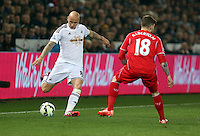 SWANSEA, WALES - MARCH 16: L-R Jonjo Shelvey of Swansea takes a cross over Alberto Moreno of Liverpool during the Premier League match between Swansea City and Liverpool at the Liberty Stadium on March 16, 2015 in Swansea, Wales