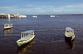 Manaus, Brazil. Small river boat water taxis moored with large gaiola riverboats behind.