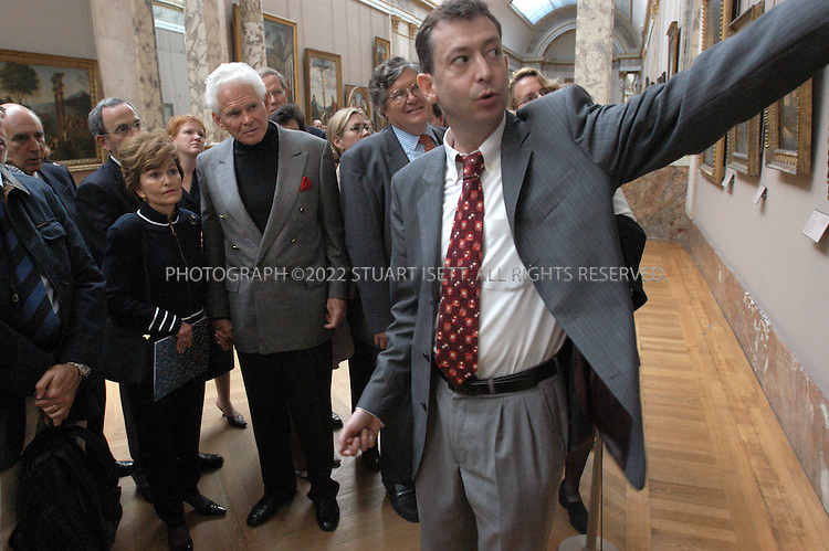 9/14/2004--Paris, France..Jacques Le Roux, right, gives a private tour of the Louvre Museum to a group of American supporters of the museum (American Friends of the Louvre) including John and Nancy Teets of Arizona (center/back: white hair, grey blazer with wife on left)...Photograph by Stuart Isett.©2004 Stuart Isett. All rights reserved