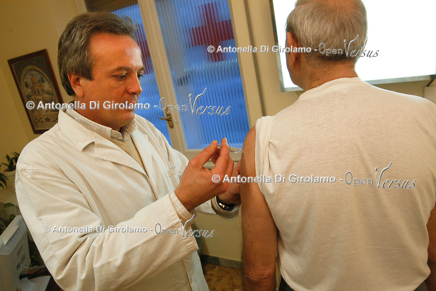 Medico somministra il vaccino antinfluenzale al un anziano. .Doctor administering the flu vaccine to an elderly person.....