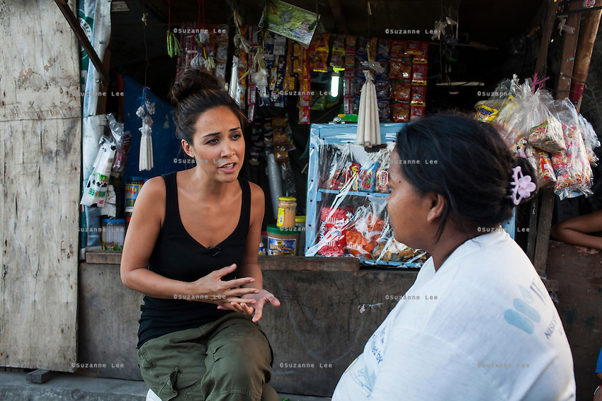 UK celebrity Myleene Klass interviews Rose Marie Ferrer, 33, in Rose's shop, selling funeral items, in an inhabited cemetery where she lives with her large family in Paranaque City, Metro Manila, The Philippines on 18 January 2013. She supports her family with income from this shop, has breastfed all her 5 children, and is 9 months pregnant now. Photo by Suzanne Lee for Save the Children UK