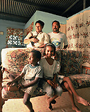 PANAMA, Bocas del Toro, portrait Tapio his family and a pet monkey in their home, Central America