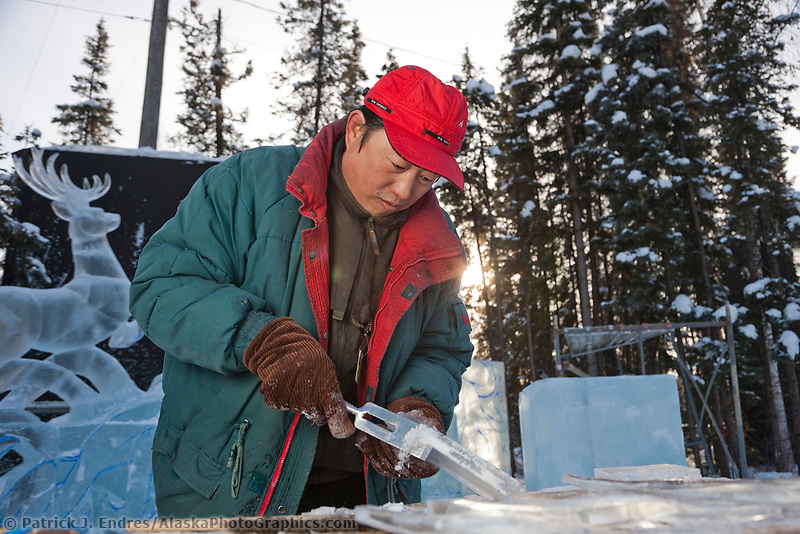 """2009 World Ice Art championships, Fairbanks, Alaska. Multi-block sculpture competition. Realistic category, titled """"The Song of the Earth"""" by Chinese sculptors: Wei,Tian Zuo; Feng,Yan Long; Chang, Chun He; Li, Hai. Fen Yan Long carves ice details."""