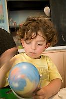homeschooling, educazione parentale. Nicholas gioca con il mappamondo
