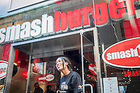 An employee greets customers at the door of the new Smashburger restaurant in the shadow of the Empire State Building in New York on its grand opening day, Thursday, April 10, 2014. The popular Colorado chain, which has a cultish following, opened its first Manhattan outpost  bringing their burgers, smashed to order to the Big Apple. The fast casual restaurant has a loyal fan base and has 260 restaurants worldwide. The franchise welcomed their Manhattan customers by offering a free Classic Smashburger to each patron all day, with the line eventually stretching around the block.  (© Richard B. Levine)