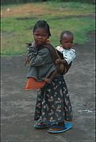 Girl carrying her sibling on her bacck. Rhonda slum, Nakuru, Kenya.