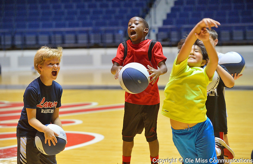 Raif Long, left, and Keion Dunlap cheer as Karson Guest shoots a free-throw during a basketball camp. Photo by Thomas Graning/Ole Miss Communications