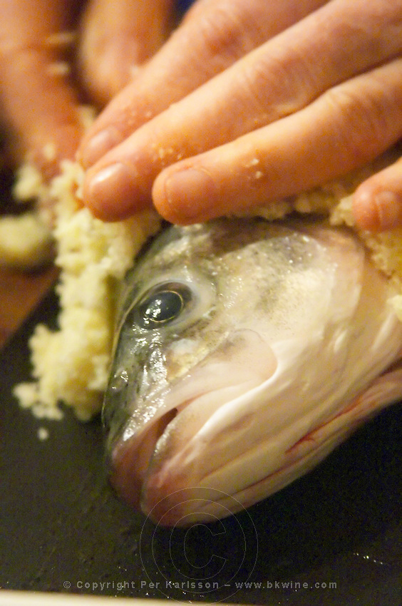How to prepare fish baked in the oven in salt crust (en croute de sel), recipe, series of pictures: head of fish in close up being covered with salt by two hands Clos des Iles Le Brusc Six Fours Cote d'Azur Var France