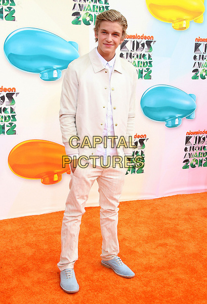 Cody Simpson.2012 Nickelodeon Kids' Choice Awards held at the Galen Center, Los Angeles, California, USA, 31st March 2012..full length white shirt cream jacket  trousers hands in pockets  blue shoes .CAP/ADM.©AdMedia/Capital Pictures.