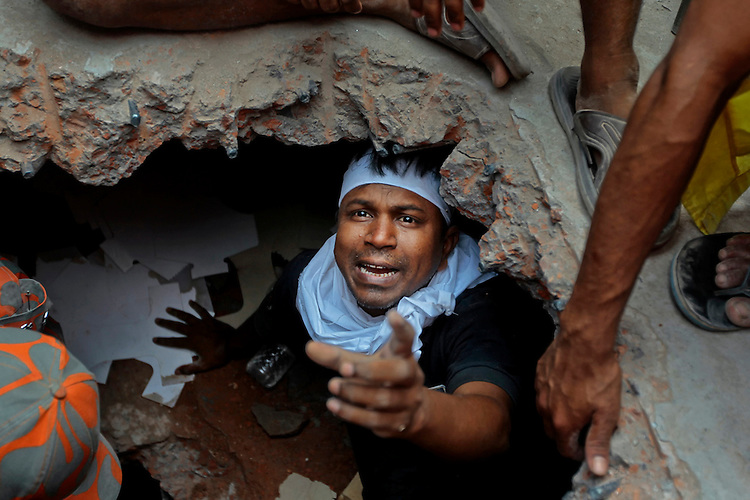 A Bangladeshi rescuer looking for survivors gestures from beneath a concrete slab of a building that collapsed Wednesday in Savar, near Dhaka, Bangladesh,Thursday, April 25, 2013.