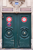 A pair of large green gates in Paris marked with the street number 20 and safety warning.