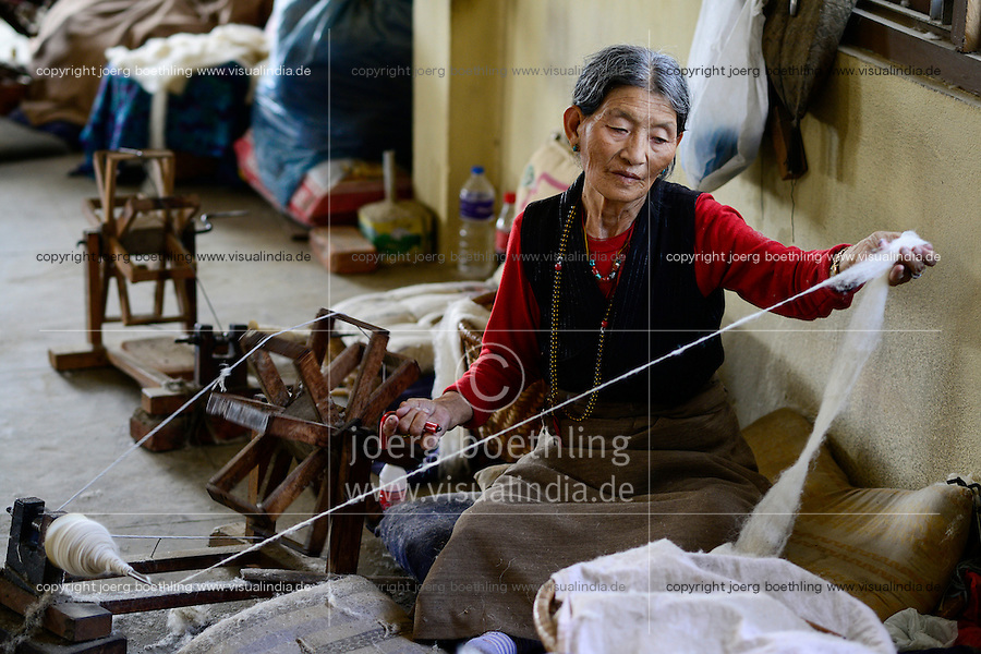 NEPAL Kathmandu, Lalitpur, tibetan refugee camp Jawalakhel, carpet factory JHC Jawalakhel Handicraft Center, tibetan women spin wool for carpets for income generation /  tibetische Fluechtlinge, tibetisches Fluechtlingslager Jawalakhel, Teppichfabrik JHC Jawalakhel Handicraft Center, tibetische Frauen spinnen die Wolle