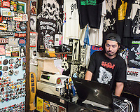 A salesperson in a shop selling goods for rock and metal fans.