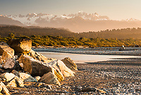 Spectacular sunset views of Southern Alps from beach near Okarito. Mt. Tasman and Aoraki Mt. Cook, Westland Tai Poutini National Park, South Westland, West Coast, UNESCO World Heritage Area, New Zealand, NZ