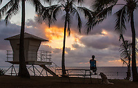 Woman sitting on picnic table next to her dog watching sunset at Haleiwa beach park with standup paddler in the water.
