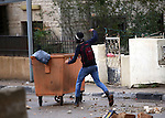 A Palestinian protester throws stones towards Israeli security forces during clashes next to the Jewish settlement of Psagot, near the West Bank city of Ramallah, November 3, 2015. The current wave of violence erupted in mid-September, fueled by rumors that Israel was trying to increase Jewish presence in Jerusalem then quickly spread across Israel, the West Bank and the Gaza Strip. Photo by Shadi Hatem