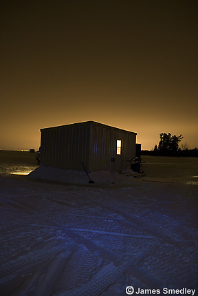 Ice fishing hut on a frozen lake in winter