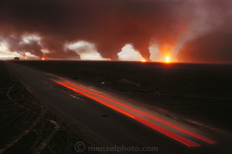 A car's tail lights make red steaks down a road in the burning northern Al-Rawdhatain oil fields in Kuwait after the end of the Gulf War in May of 1991. More than 700 wells were set ablaze by retreating Iraqi troops creating the largest man-made environmental disaster in history.