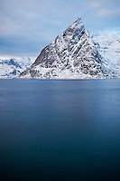 Olstind mountain peak rises from Kjerkfjord in winter, Lofoten islands, Norway