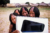 Bacaja village, Amazon, Brazil. Four girls with shaved heads holding onto the door of a plane; the village airstrip; Xicrin tribe.