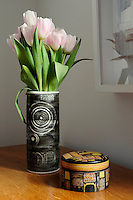 An simple arrangement of pale pink tulips is set off by the grey and white vase. A small wooden trinket box stands next to it.